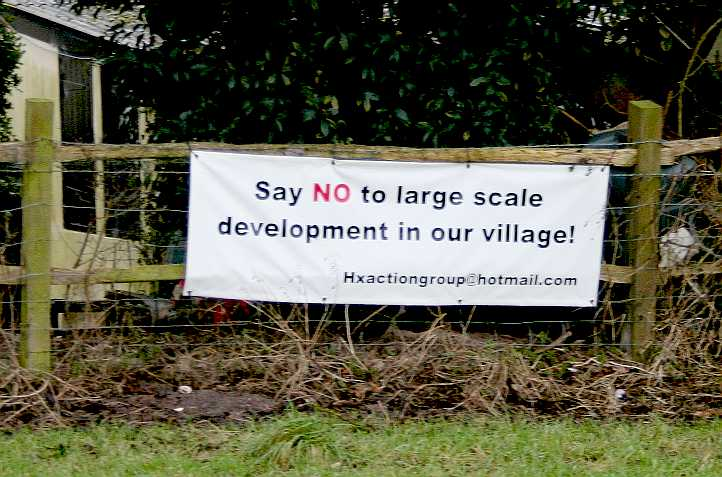 Protestors sign objecting to 70 house application